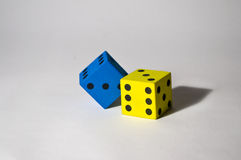 Foam dice. Blue and yellow foam dice on uncluttered background Royalty Free Stock Photos