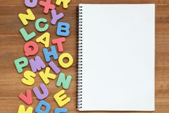 Foam english alphabet letters with open blank page notebook on w Royalty Free Stock Images