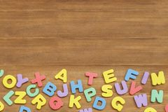 Foam english alphabet letters on wooden background Royalty Free Stock Photos