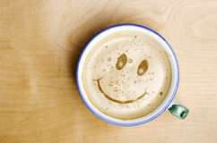 Foam form of smile face in cup of Cappuccino Coffee on wooden ta Royalty Free Stock Photography