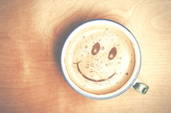 Foam form of smile face in cup of Cappuccino Coffee on wooden ta Stock Image