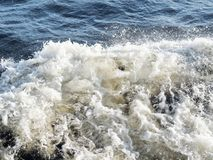 Waves formed from the propeller of the ship. Foam formed on collisions of waves Stock Images