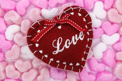 Foam hearts background with felt heart in the center. Background with pink, peach and white foam hearts and red felt heart in the center royalty free stock photography