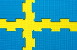 Foam interlocking yellow and blue floor tiles in the shape of the Swedish flag. Yellow and blue gym floor tiles / exercise mats in the shape of the Swedish flag royalty free stock photography