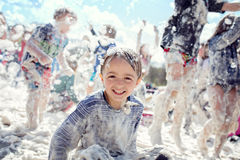 Foam party and summer fun in the sun. Boy smiling and laughing covered in soad suds at a summer foam party stock image