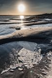 Foam in a puddle left by low tide at sunrise. Sunrise over the mud and the foam that formed on a puddle at low tide in the Bay of Somme Royalty Free Stock Photos