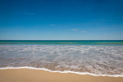 Foam on Sand. Landscape view of small breaking wave on beach with foam on the sand, against a calm sea and a bright blue sky royalty free stock photography