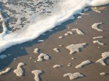 Foam on sandy beach Royalty Free Stock Image