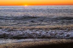 Foam sea wave rushes onto seashore at sunset Royalty Free Stock Photo