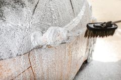 Foam and shampoo spraying from brush to side mirror of a car in royalty free stock images