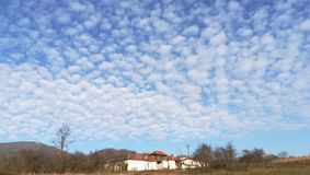 Foam in the sky of clouds. Strange clouds of the fate of a village. Sunny day in January. Great beauty of nature Royalty Free Stock Photo
