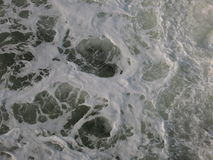 Foam stirred sea background in white, blue and grey stock photography