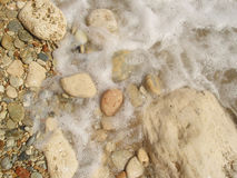 Foam and stones Stock Images