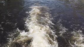 Foam trail behind the stern of a motor boat or excursion tourist ship