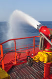 Foam/water gun in action. Fire fighting foam/water gun onboard of tanker ship stock photo