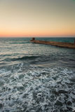 Foam on the water at sunset. A traquil sea with small foamy waves and a breakwater at sunset Stock Photos