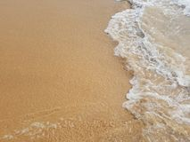 Foam Wave. A foamy sea on the wet sand of a large beach Stock Photo