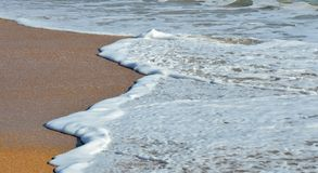 Foam waves on sandy beach Royalty Free Stock Photography