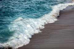 Foamed waves breaking in the beach Royalty Free Stock Images