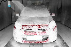 Foaming red auto at car wash stock image