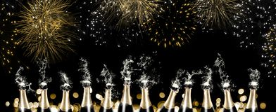 Foaming and splashing champagne bottles with fireworks. A row of 12 champagne bottles sputtering with liquid and foam in front of a black background with Royalty Free Stock Photos