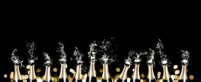 Foaming and splashing champagne bottles panorama. A row of 12 champagne bottles sputtering with liquid and foam in front of a black background with golden bokeh Stock Photos