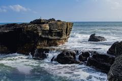 Water and rocks. Powerful. Waves on a rocky beach. High cliff above the Ocean, summer background, many splashing waves. Foaming white backwash from the Indian royalty free stock photos