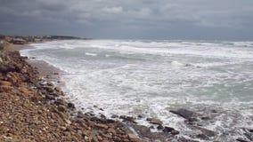 Foamy θυελλώδης ρόλος κυμάτων στη ρηχή παραλία άμμου με τους βράχους φιλμ μικρού μήκους
