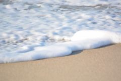 Foamy πλύσιμο κυμάτων επάνω επάνω στην αμμώδη παραλία Στοκ εικόνα με δικαίωμα ελεύθερης χρήσης