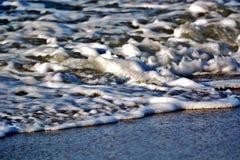 Foamy πλύσιμο κυμάτων επάνω επάνω στην αμμώδη παραλία Στοκ Εικόνα