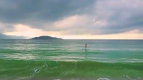 Foamy ρόλος κυμάτων στην παραλία και κορίτσι στο paddleboard στον ωκεανό απόθεμα βίντεο