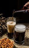 Foamy beer from bottle poured into glasse standing with mug beer with wheat and basket of pretzels Stock Image