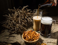 Foamy beer from bottle poured into glasse standing with mug beer with wheat and basket of pretzels Royalty Free Stock Photography