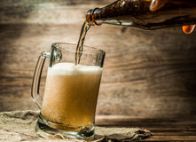 Foamy beer from bottle poured into mug Stock Image