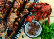 Foamy beer in a glass and boiled crawfish closeup, grilled meat on skewers in the background. The top view. Royalty Free Stock Photo