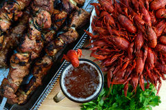 Foamy beer in a glass and boiled crawfish closeup, grilled meat on skewers in the background. The top view. Royalty Free Stock Photography