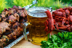 Foamy beer in a glass and boiled crawfish, grilled meat Royalty Free Stock Photo