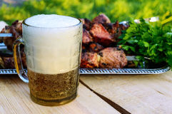 Foamy beer in a glass closeup grilled meat on skewers in the background. Stock Images