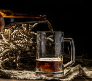 Foamy beer poured into mug standing on empty wooden background Royalty Free Stock Photos