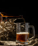 Foamy beer poured into mug standing on empty wooden background Stock Image