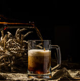 Foamy beer poured into mug standing on empty wooden background Stock Photography