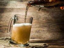 Foamy beer poured into mug standing on empty wooden background. Foamy beer from bottle poured into mug standing on empty wooden background Stock Image