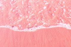 Foamy clear sea wave rolling to pink sand shore beach. Aerial view from above. Beautiful tranquil idyllic scenery. Tropical nature