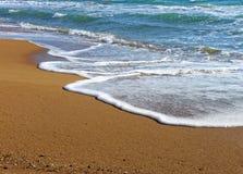 Foamy fala denny chełbotanie na piaskowatej plaży Obraz Royalty Free