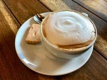 Foamy filiżanka kawy Cappuccino z ciastkiem na Drewnianej powierzchni słuzyć przy restauracją obrazy royalty free