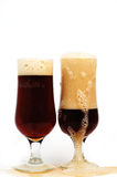 Foamy  glass dark beer. Two  Glasses  dark beer ,brimming over  white  background Royalty Free Stock Images