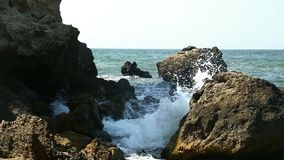 Βράχοι για τους οποίους foamy κύματα θάλασσας σπασιμάτων απόθεμα βίντεο