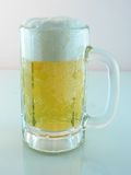Foamy Ice cold beer. Ice cold beer with reflection and reddish background stock images