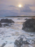 Foamy Sea. Evening sun sinks low in sky,as stormclouds gather Stock Images