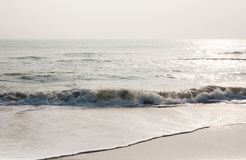 Foamy waves on calm beach. Foamy sea waves on a calm tropical beach in the morning Stock Photos